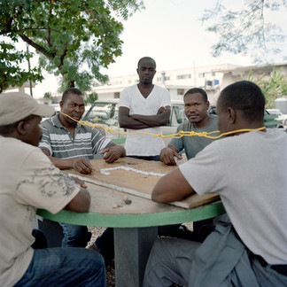 """A game of dominos among police officers who are in charge of the security for the president. The losers of the game are designated as """"dogs"""" and forced to wear something that attracts the ridicule of passersby. Here, they are tied together with electric wire. Presidential Palace, Port-au-Prince. Haiti"""