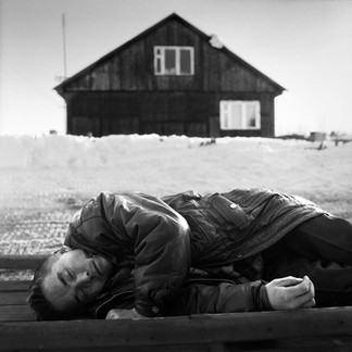 A Khanti sleeps off his drinking on a sledge in front of the house given to him by oilmen in exchange for his ancestral lands in the forest. Death stalks those who sleep outside: in the winter it's the cold that kills, in the summer mosquitoes.