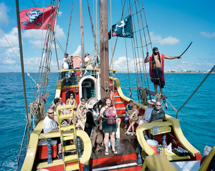 """Besides being one of the world's major offshore centers, the Cayman Islands are also a prime tourist destination, attracting low-cost cruise ships travelling to the Caribbean. Tourists disembark on the island for one day and are offered a range of attractions including a one-hour all-drinks-included """"pirate ship trip,"""" with Jamaican immigrants playing the pirates. Grand Cayman"""