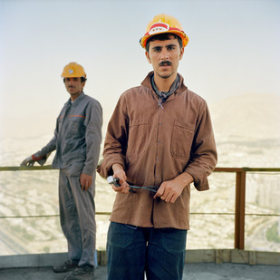 Two construction workers on the top of the Milad Tower. The Milad Tower is the tallest tower in Iran and the fifth tallest tower in the world standing at 435 m. Sweeping views of the city are marred by Tehran's choking pollution caused by ancient cars running on cheap government subsidized petrol.  Most of the low paid workers, like the two photographed, are ethnic Turks from north-west Iran, or from A   fghanistan. Iran, Tehran, August 2006.