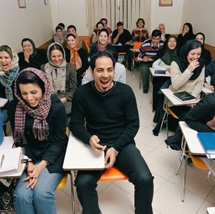Mr Mohtashemi runs the Laughing School from his small office in North Tehran. Mohtashemi learnt his techniques from an Indian method, which believes that the physical act of laughing has positive effects on people's well being and self confidence. In these classes, Mohtashemi first guides his students through laughing exercises, followed by lectures modeled on American self help master, Anthony Robbins. Students pay $200 a year to attend his courses.  Iran, Tehran, December 2006.