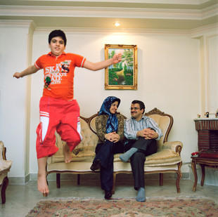"""Ali Reza Dekhan, 42, and his wife Akramossadat, 35, photographed here with their elder son Hassan, 11, have been introduced to each other 13 years ago by their parents. They got married without knowing each other. At the beginning, they say, there was no love, just a rational choice based on criteria like education, social position and common views on religion and women's rights. Love came after a few years and is now growing day by day. Friends of Ali Reza, who are less fortunate in their marital life, keep asking him what is his secret. """"Love, he answers, is like a small flower. You've got to water it and pay attention to it every day, otherwise it will die overnight"""". Iran, Tehran, February 2009."""