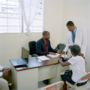 The office of the Justice of the Peace, Jean Michelet Seide. A plaintiff registers a complaint against her husband who hit her the night before with a metal plate that she has with her as proof. The computer, supplied by Canadian aid, is not used. The complaint is written out by hand. Les Cayes. Haiti