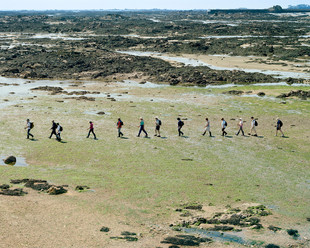 """Trudie Hairon, a guide with Jersey Walk Adventures, leads a group of tourists for a """"Moonwalk,"""" on a patch of seabed that can only be explored at low tide. The British crown dependency of Jersey experiences tides of up to ten meters, some of the world's most dramatic, exposing kilometers of land that are covered by the ocean the rest of the time. Jersey"""