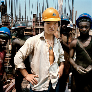 On the building site of the Imboulou dam, Republic of the Congo, 200km north from the capital Brazzaville. In the foreground a Chinese worker of the China National Mechanical & Equipment corporation (CMEC) company, which has obtained the contract in 2001. With its 120 megawatts, this power plant will double the national production of electricity and will give light to a large part of Congo. 400 Chinese technicians and qualified workers supervise a Congolese workforce of a thousand men, paid 3 dollars a day, who disappear as quickly as they find a better paid job. This, in part, explains the dam's construction delay that has to be absolutely terminated by 2009, the year of the next Congo elections. CMEC requires the Chinese workers to wear yellow and the Congolese blue hardhats.