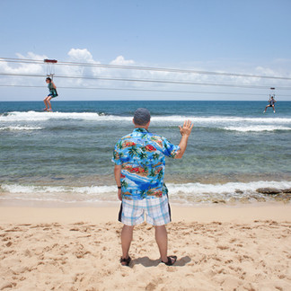 An American tourist waves to his daughter as she goes by on a zip line from the hills above Coco Beach. They will spend a day on this private beach before boarding their cruise ship that has made a stop in the bay. Labadie.