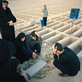 At the graveyard of Behesht-e-Zahra, in the very south of the city, a family morns their father who has just been buried. Behind them a paid singer ads to the mourning standing between the empty tombs in the new section of this enormous cemetery. Iran, Tehran, June 2005.