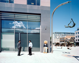 """Businessmen have a chat in front of Liberation House, an office building occupied by financial institutions. They both work for Computer Sciences Corporation, an American multinational that has offshore clients in Jersey to whom it provides consultancy and software development services. On the right hangs """"Jersey Girl,"""" a sculpture by Rowan Gillespie, its base inscribed with the Thoreau quote, """"All good things are wild and free."""" Jersey"""