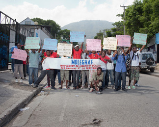 """In front of the Ministry of Social Affairs, a demonstration for jobs organized by the Moleghaf (the Haitian Movement for Freedom and Equality in Brotherhood). On the placards, slogans in Creole denounce """"the bourgeois State,"""" """"State corruption,"""" """"the high cost of living"""" and """"hunger."""" Port-au-Prince. Haiti"""
