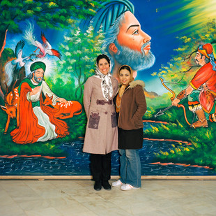 Sally, on the right, and her friend Banafsheh in a photographer's studio in the city of Mashhad. Sally has come to Mashad to thank the Imam Reza, buried here and one of the holiest figures Shia Islam, for helping her to get a satisfactory divorce. The painting behind them represents the Imam Reza saving a gazelle.  Iran, Mashad, December 2006.