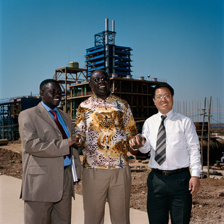 Wang Xin one of the men in charge for the free trade zone of Chambishi that is being created in the heart of the Copperbelt, has his photograph taken with two Zambian deputies who have come to investigate on this giant project that will include the copper smelter that is in construction behind them. This smelter represents a 300 million dollar investment and is one of the leading projects of the Chinese in Zambia but it's construction has been slowed down by strikes of workers protesting wages of less than 200 dollars a month that have been violently repressed by the Chinese security agents.