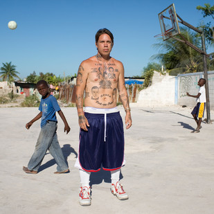"""Jason William Petrie, known as """"Zeke,"""" age 39. Born in Ohio in the United States, he lived for over 20 years in the Cité Soleil district before being forced to leave, suspected of wanting to bring back the Haitian army. His body is covered with patriotic Haitian tattoos, including the country's flag. Cité Soleil. Haiti"""