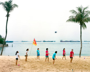 """Girls from a local school play volleyball on the beach in Sentosa, an island resort that defines itself as """"Asia's favorite playground."""" Dozens of tankers are anchored just off the coast in the Singapore Strait. Local traders joke that they can keep track of the fluctuations of the market simply by looking at the number of oil tankers waiting to unload at the mouth of the harbor. Singapore"""
