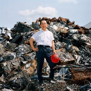 """Mr. Y. T. Chu in front of the scrap metals that will feed his steel plant, Federated Steel at Ota in the Ogun state. Mr. Chu arrived in Nigeria at the beginning of the 80's. Full of nostalgia he recalls the time of the numerous military coups.  """"Each new dictator would void the commenced projects of the former and would launch his own"""" he says """"the steel we would recover on the interrupted worksites was of great quality, we would melt it and sell it with large margins. But things are not bad today either. We still cannot fulfill the demand for construction iron""""."""