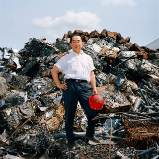 "Mr. Y. T. Chu in front of the scrap metals that will feed his steel plant, Federated Steel at Ota in the Ogun state. Mr. Chu arrived in Nigeria at the beginning of the 80's. Full of nostalgia he recalls the time of the numerous military coups.  ""Each new dictator would void the commenced projects of the former and would launch his own"" he says ""the steel we would recover on the interrupted worksites was of great quality, we would melt it and sell it with large margins. But things are not bad today either. We still cannot fulfill the demand for construction iron""."