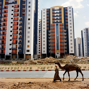 A young nomad walks by with his camel in the brand new neighbourhood of Bananier Bis. Here the Chinese construction company CSCEC is building thousands of apartments for the Algerian government that is facing an unprecedented housing shortage. CSCEC has built 30.000 of the 55.000 apartments of the nation's wide housing project.