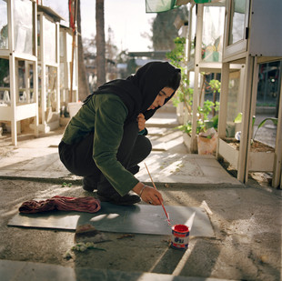 Each Friday, in the Behest Zahra cemetery, Fereshteh, 22, cleans, paints and decorates the graves of the Unknown Soldiers of Iran-Iraq war. She has not been asked to do this and nobody in her direct family has fallen in the conflict. Iran, Tehran, February 2009.