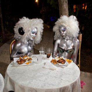 At the Hôtel Karibe, above Port-au-Prince, two go-go girls dig into fried chicken after dancing for hours at the concert of a local singer, J Perry. Juvénat, Pétion-Ville. Haiti