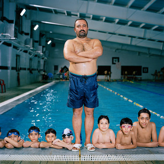 Hajji, 46, was only 20 when he volunteered for an underwater mission on the Karun River during Iran's war with Iraq. He was reserve goalkeeper on the national water polo team, but was captured and spent nine years in a prisoner of war camp in Iraq. He finds it difficult to talk about the experience, which left him permanently scarred: 'they hardly fed us. I lost twenty five kilos.'   When he returned home he was made manager of the prestigious Martyr Shahrudi swimming pool, and later became coach of the national swimming team.  Following a disagreement with Iran's Swimming Federation Hajji is now officially retired, but coaches a junior boy's team in a women's pool in the evenings.  'I don't charge a penny for my work,' he says.  'All I wanted was to see my boys beat the federation team.  And they did.' Iran, Tehran, August 2006.