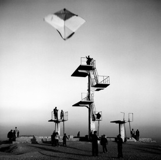 In 1979 the Russians built an Olympic swimming pool on one of the hills overlooking Kabul. Construction was finished just months before the Russian invasion of the country, but the pool has never been filled with water. Kabul children hang out here, often flying their kites.