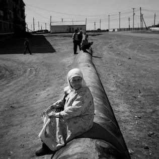 An old woman sits on a pipeline running towards the railway where oil will be loaded into containers.