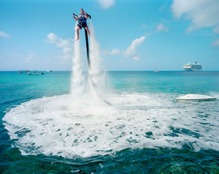 """An employee of """"Jetpack Cayman"""" demonstrates this new watersport, now available on the island. A 2000cc motor pumps water up through the Jetpack, propelling the client out of the sea (359 USD for a 30-minute session). Mike Thalasinos, the owner of the company, remarks, """"The Jetpack is zero gravity, the Cayman are zero taxes, we are in the right place!"""" Grand Cayman."""
