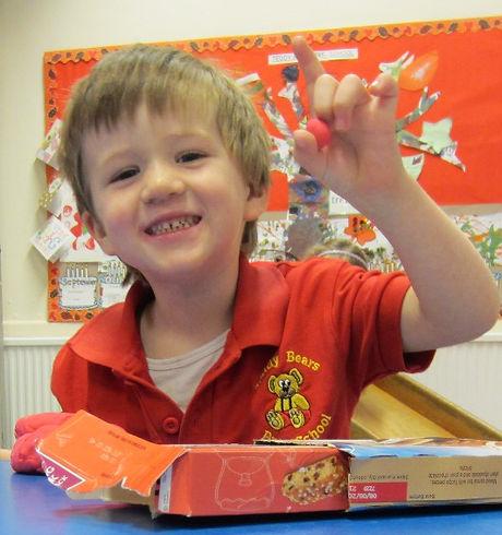 Boy having fun with playdough and cardboard
