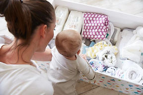 mother and baby looking over littleun baby gift box full of organic products