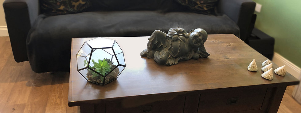 Buddha statue on wooden table with plants & shells