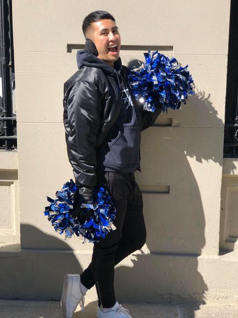 gotham cheer male cheerleader in black satin jacket with pom poms