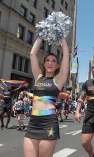 Gotham Cheer cheerleader at NYC World Pride with rainbow pom poms