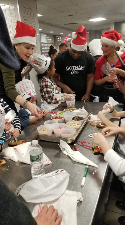 Gotham cheerleaders volunteer decorating cookies with children at God's Love We Deliver Cookie Party in NYC