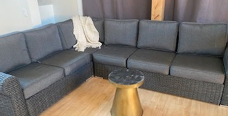 RENTAL: L shaped grey couch. Made outdoor wicker and water repellant cushions.