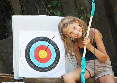 Young girl hitting archery target with retal bow.