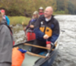This pictures shows Doug Hershman bailing water from a canoe.
