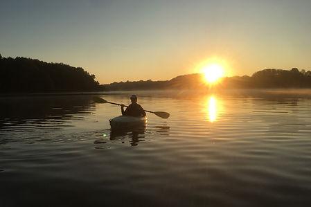 A person paddling a kayak across a lake