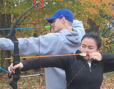 A young man and woman shooting archery w