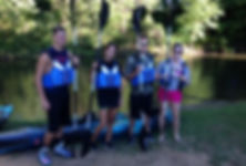 4 young people holding paddles in front