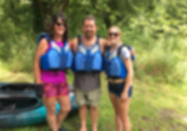 This pictures a smiling dad, mom and daughter standing with life jackets on prepared to go kayaking.