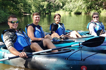 Four young adults sitting in solo kayaks