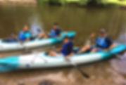 A family kayaking in tandem kayaks