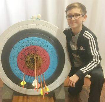 Boy kneeling next to an archery target w