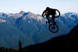 man stunt jumping on a mountain bike by mountain scenery