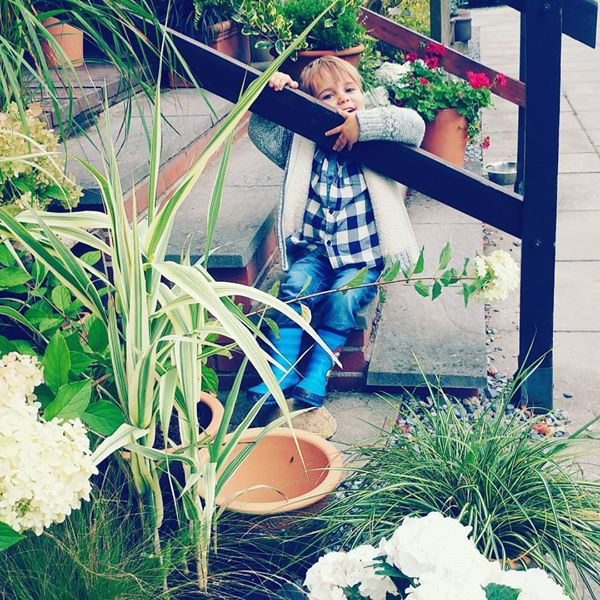 Leo smiling in an autumn fleece, plaid shirt, jeans and wellies in a garden centre surrounded by hydrangea and other potted plants.