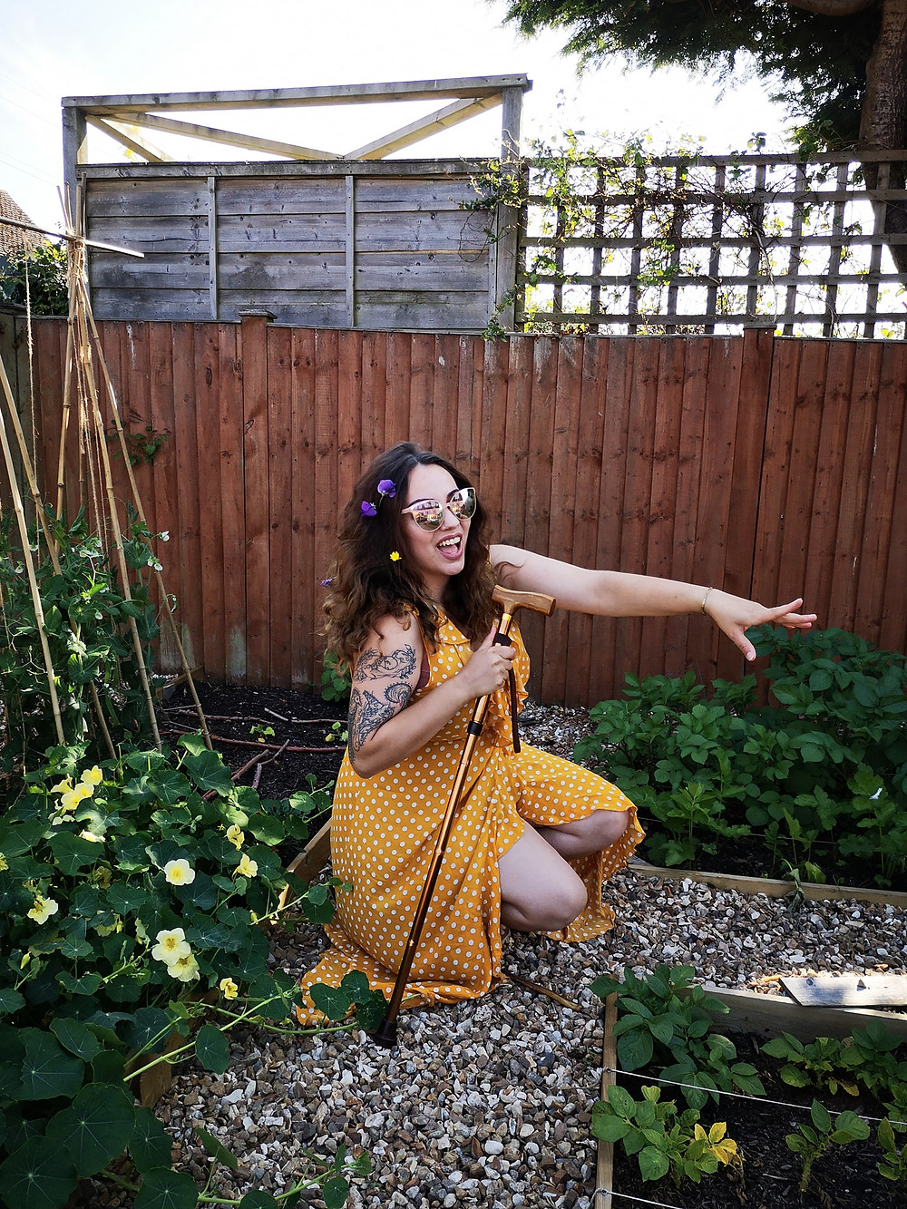 Sarah is crouching in a yellow polka dot dress, sunglasses, and sweetpeas in her curly hair, smiling and leaning on a walking stick surrounded by peas growing up canes, nasturtiums and potato plants.