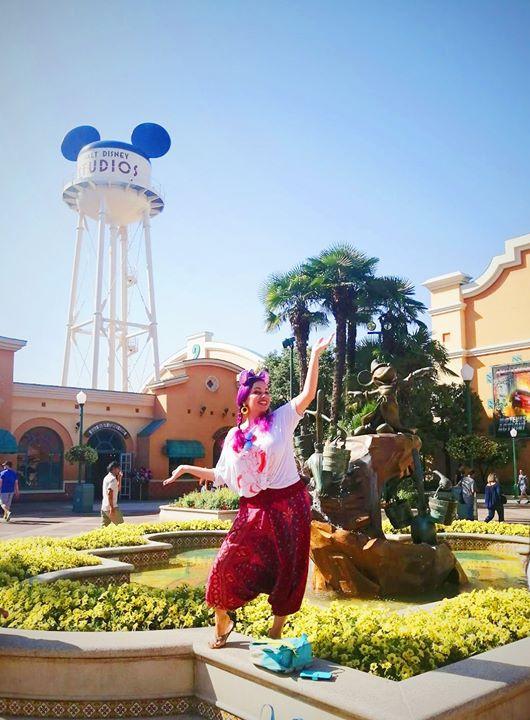 Sarah a mum blogger posing with a big smile in the sunshine at Disneyland Paris.