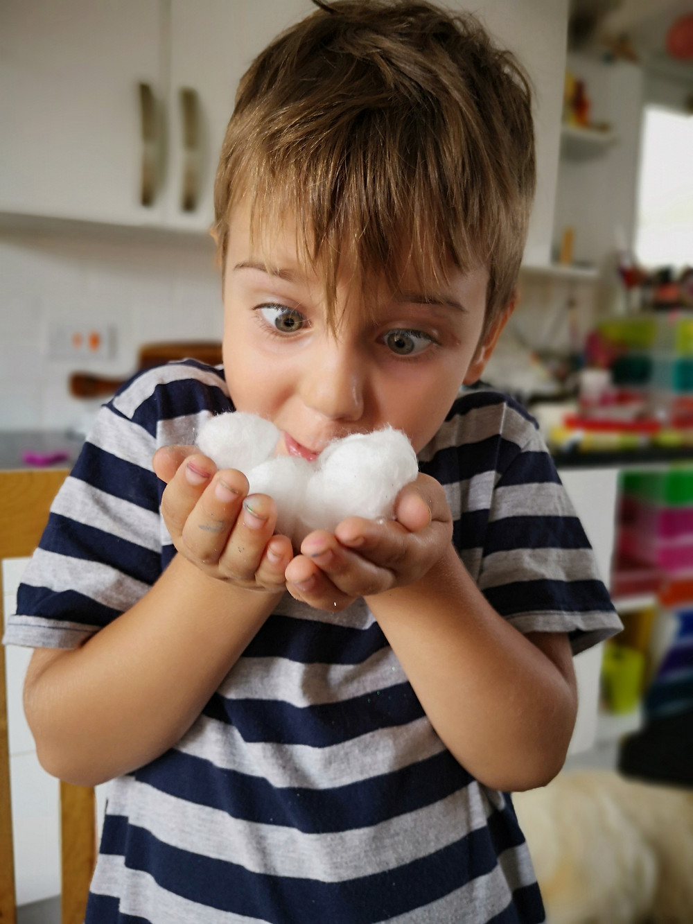 Funny kid playing with cotton wool