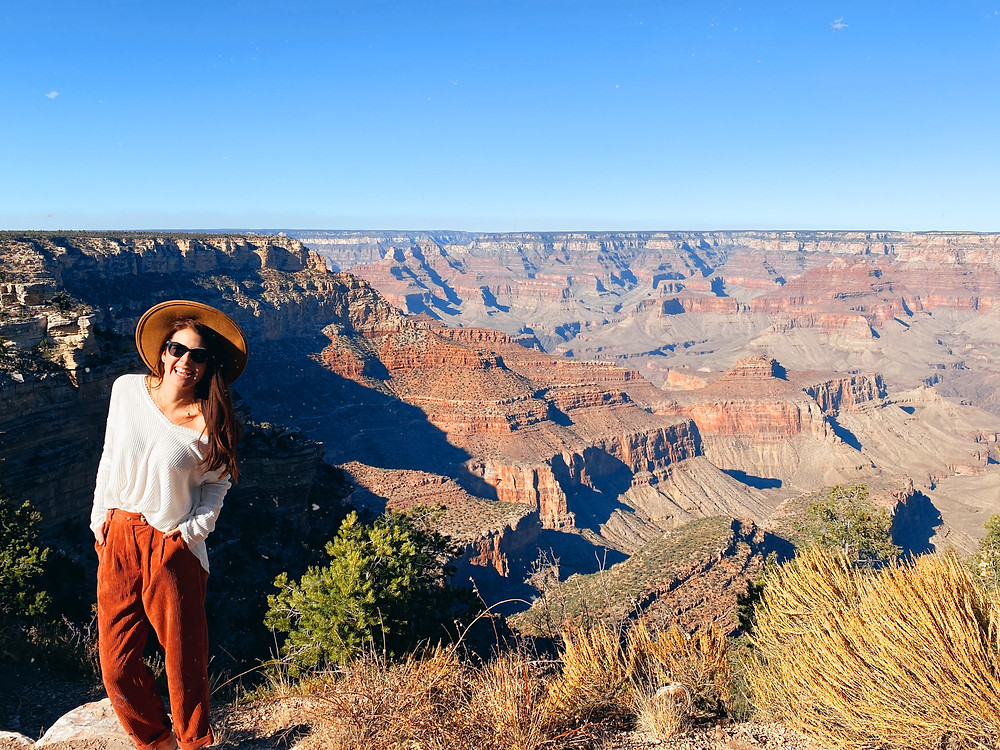 Girl stands, wide-brimmed hat and smiling, at the Grand Canyon's South Rim in Arizona
