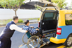 My-tti wheelchair accessible taxicab picking up a disabled wheelchair rider.