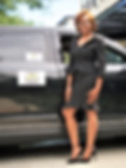 A female License Professional Chauffeur standing by  her executive Lincoln MKT.